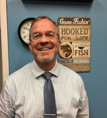 Mr. Embree in front of clock and fishing sign
