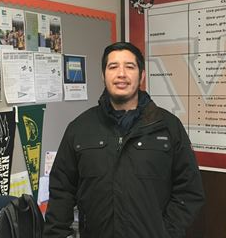 man in black jacket in front of counseling office information