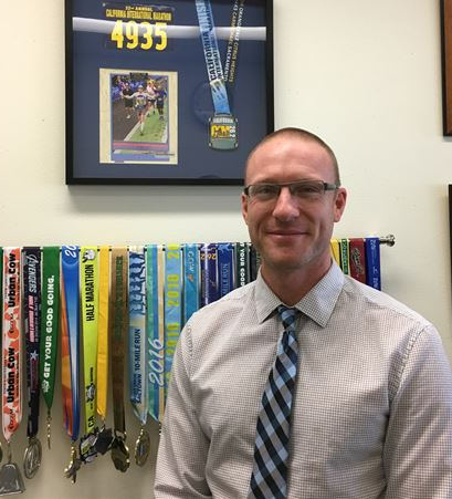 Mr. McLearan in front of running medals and awards
